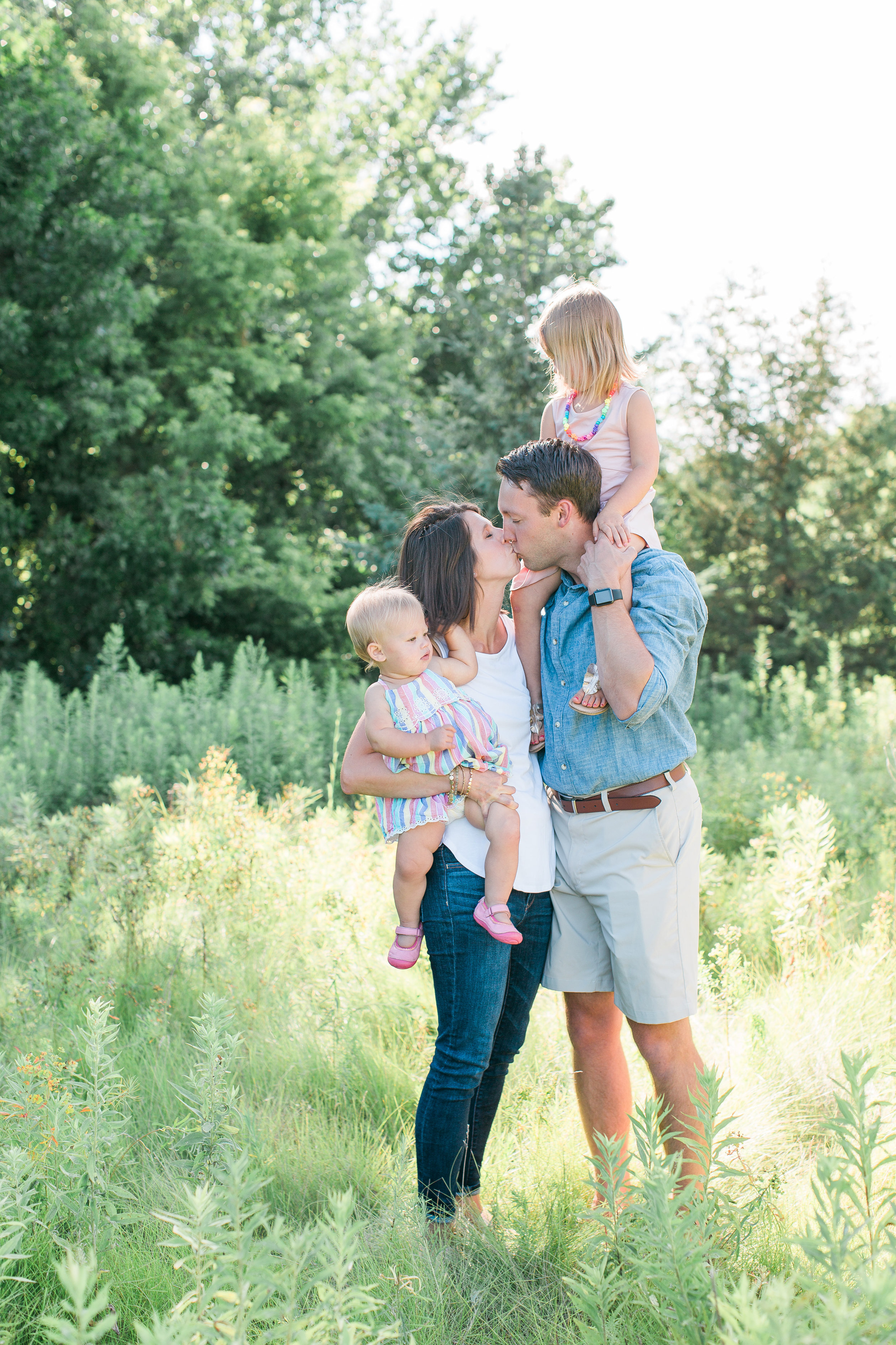 Family with husband, wife, toddler and baby in family portrait mom and dad kissing Minnesota family photographer Mallory Kiesow Photography