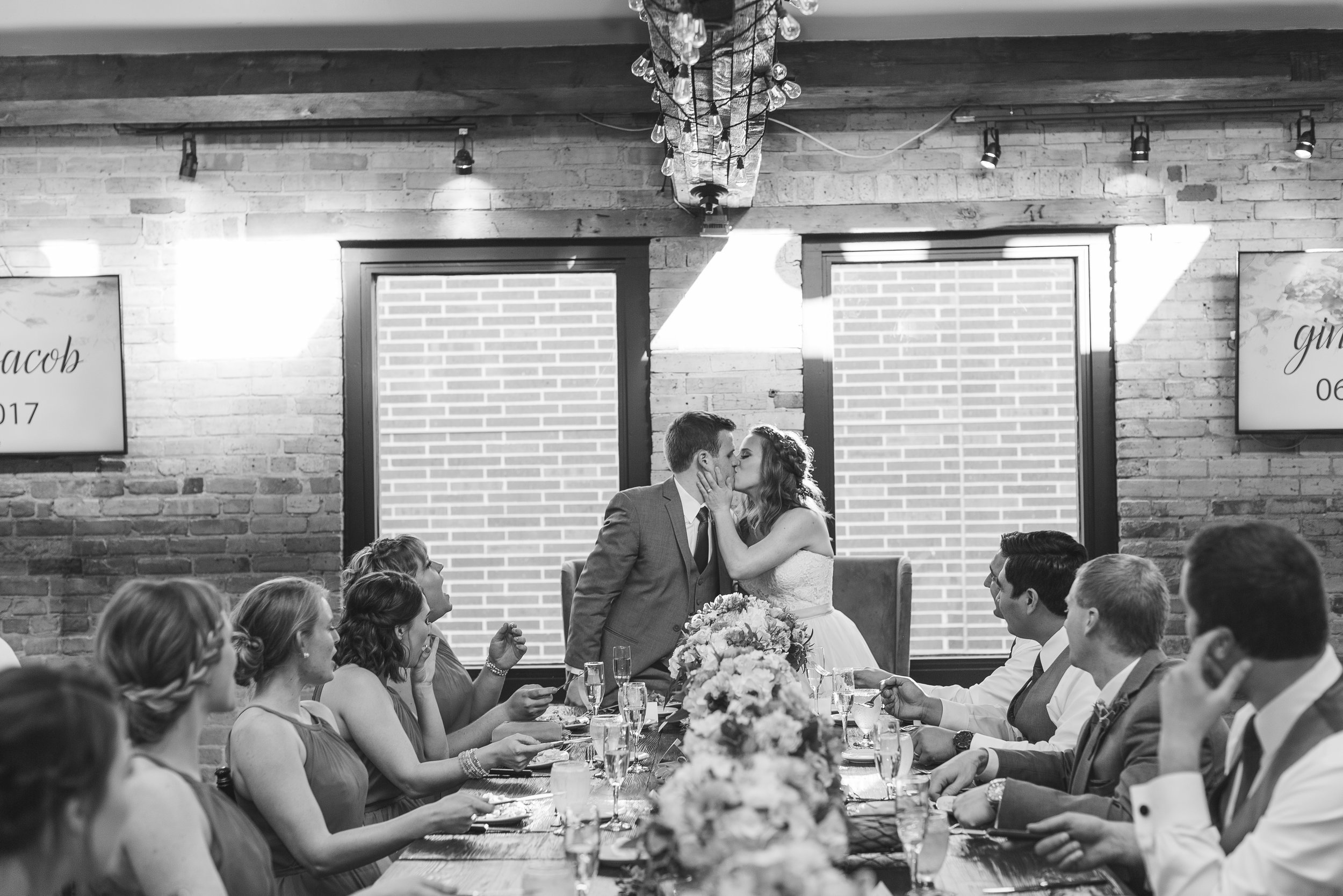 Bride and groom kissing at head table during reception in black and white at Minneapolis Event Centers wedding Minnesota wedding photography Mallory Kiesow Photography