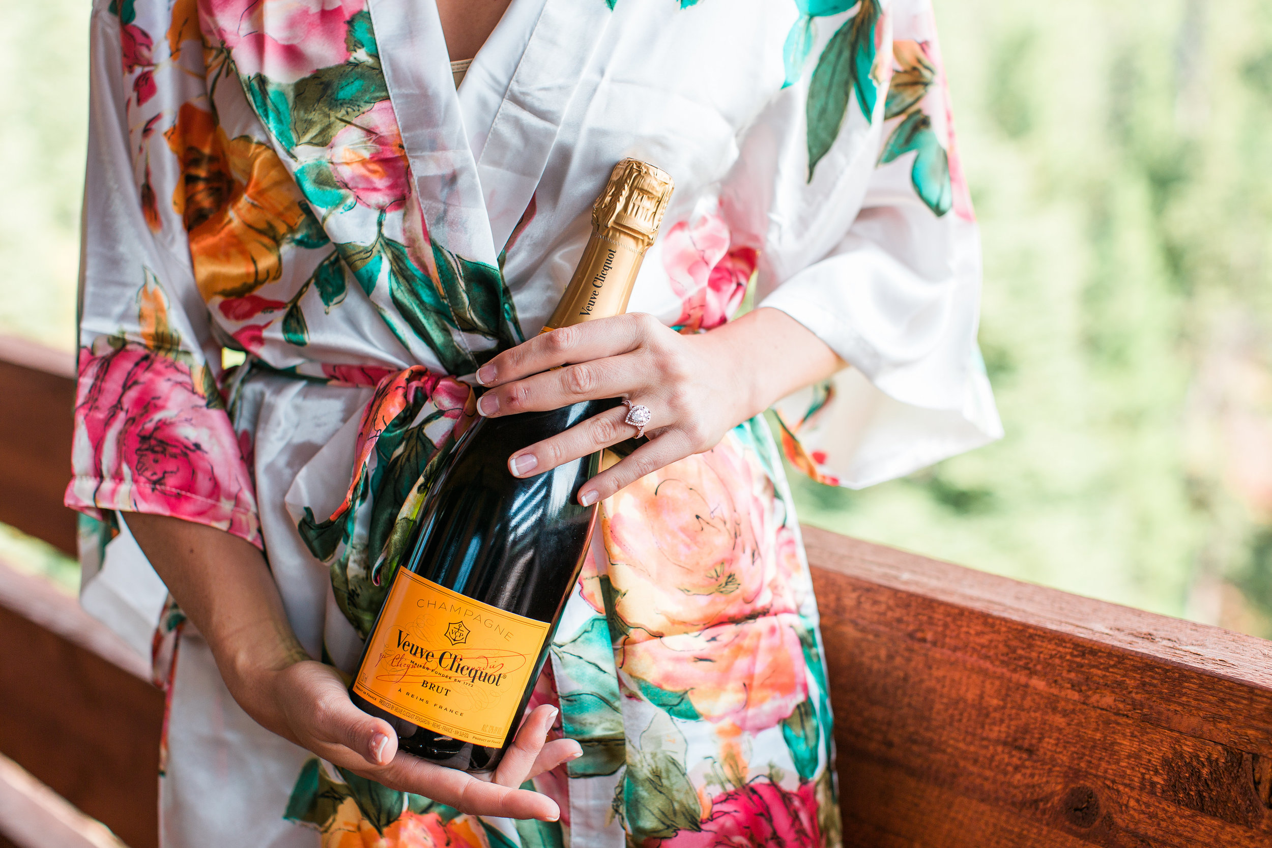 Bride with floral robe holding champagne bottle on wedding day Minnesota wedding photography Mallory Kiesow Photography