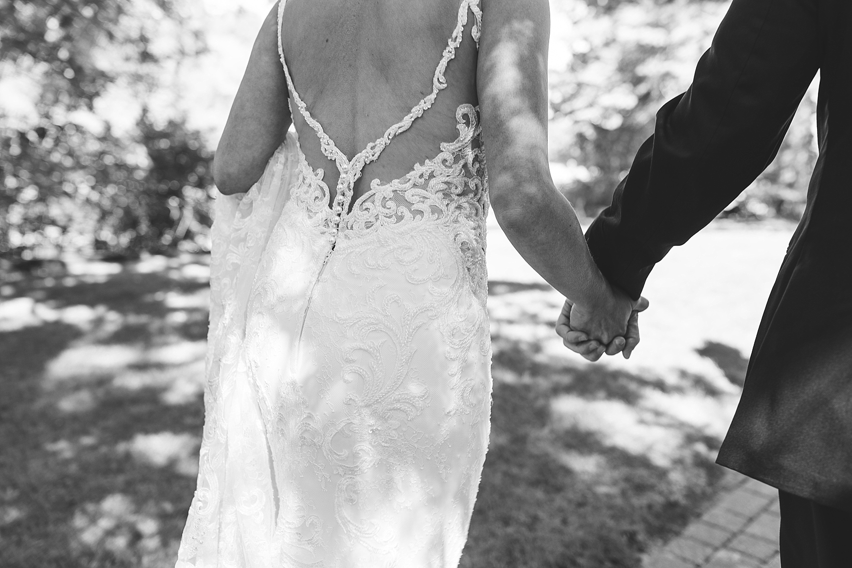 Bride and groom walking holding hands in black and white on wedding day at the Chart House Summer Wedding Lakeville Minnesota Minneapolis Wedding Photographer Mallory Kiesow