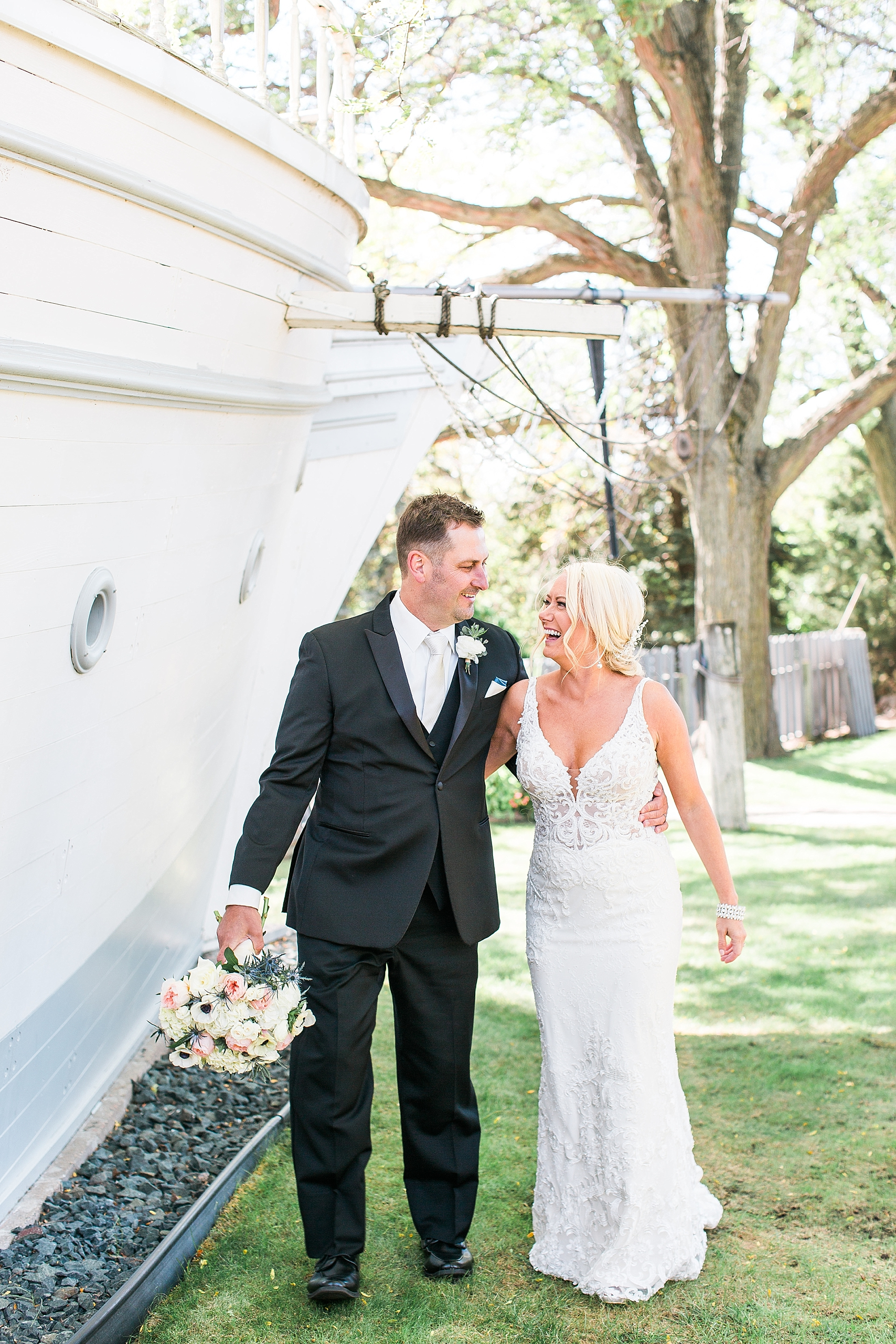 Bride and groom walking next to ship on wedding day at the Chart House Summer Wedding Lakeville Minnesota Minneapolis Wedding Photographer Mallory Kiesow
