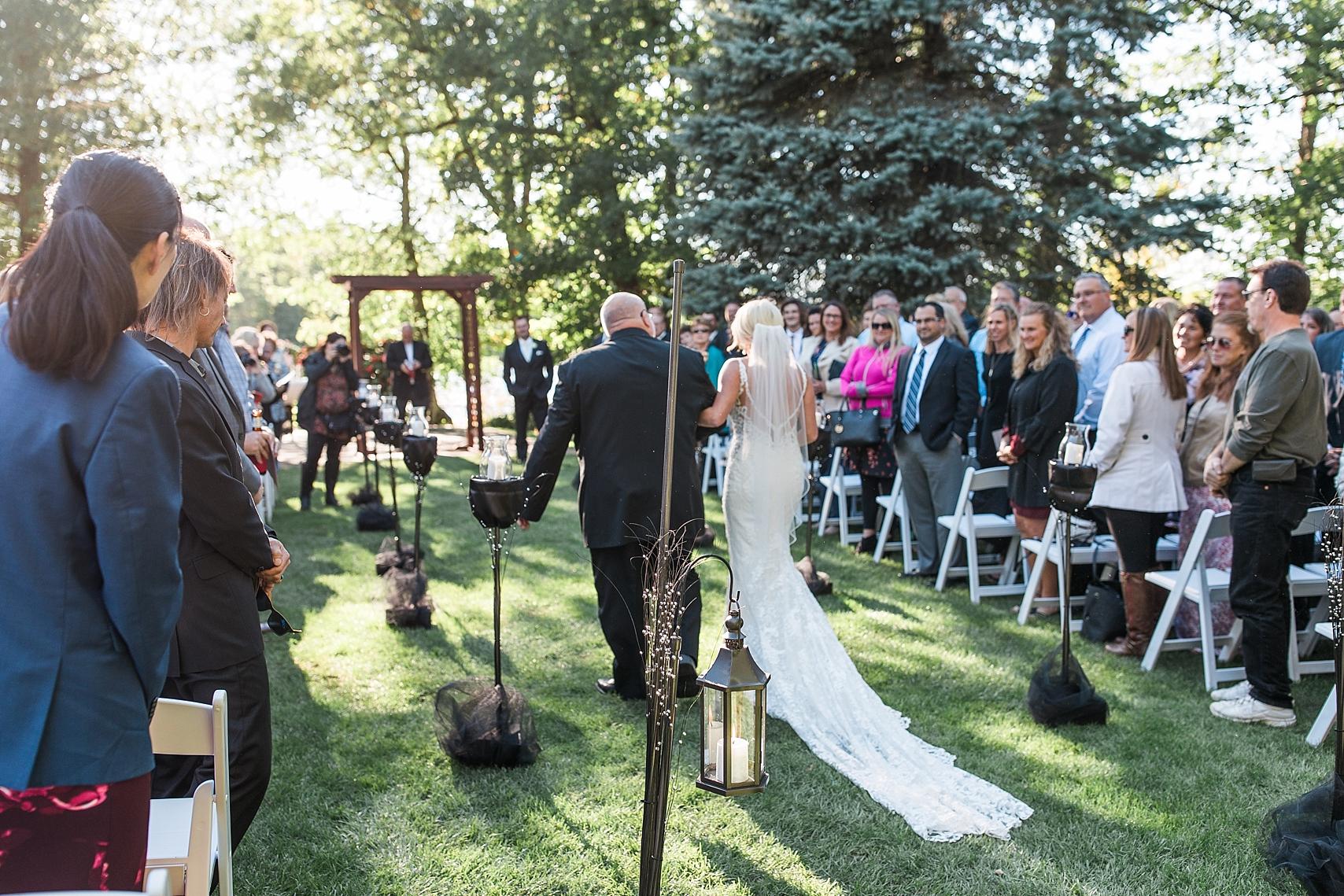 Outdoor wedding ceremony bride walking down aisle at the Chart House Summer Wedding Lakeville Minnesota Minneapolis Wedding Photographer Mallory Kiesow