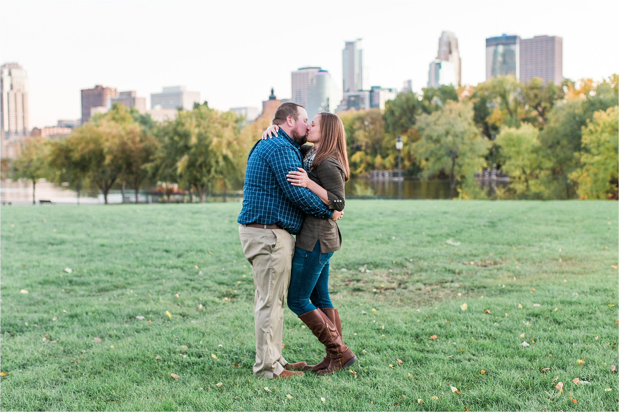 Engaged couple embracing with Minneapolis city skyline in the background at Boom Island Park in Minneapolis Mallory Kiesow Photography