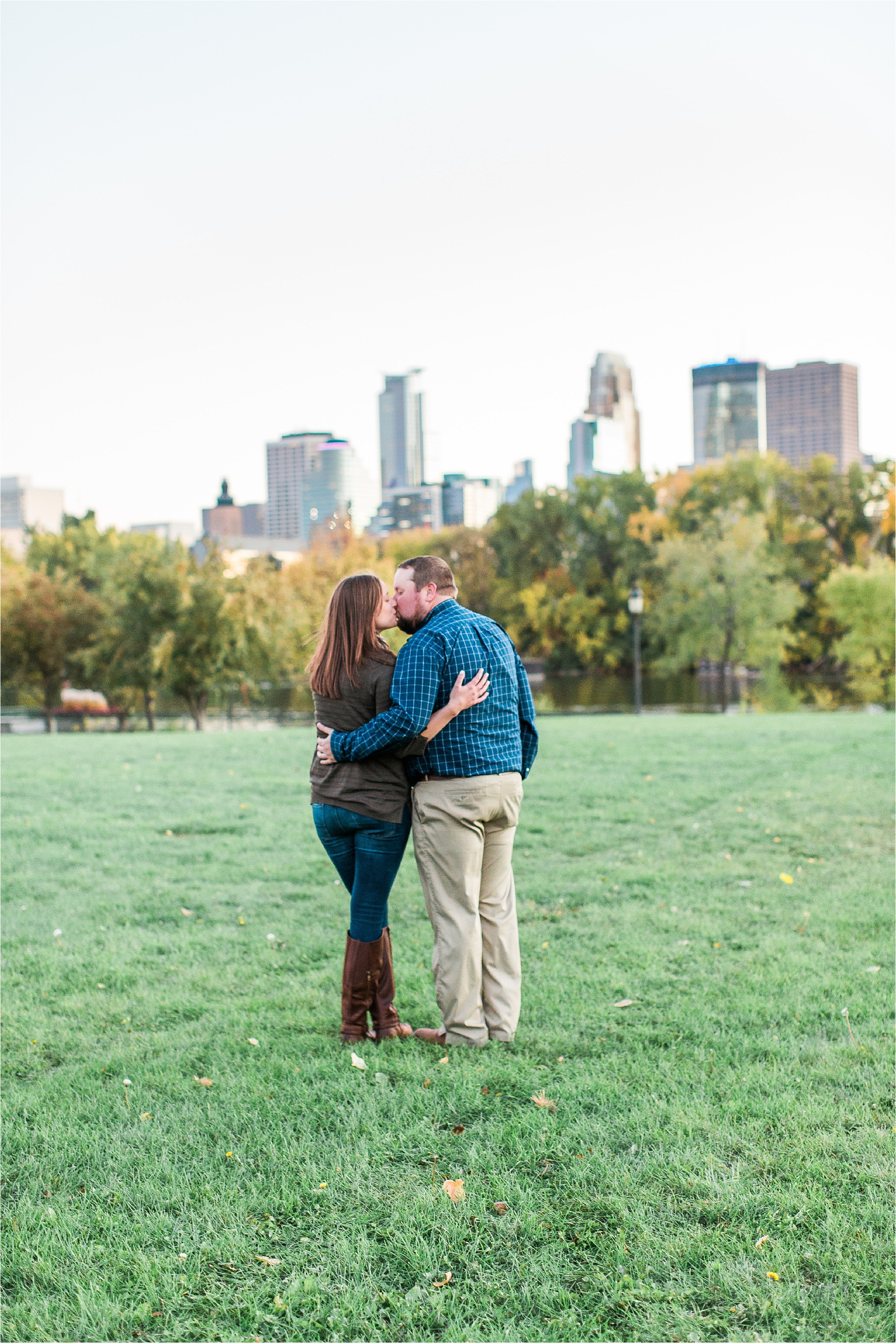 Engaged couple embracing and taking in view with Minneapolis city skyline in the background at Boom Island Park in Minneapolis Mallory Kiesow Photography