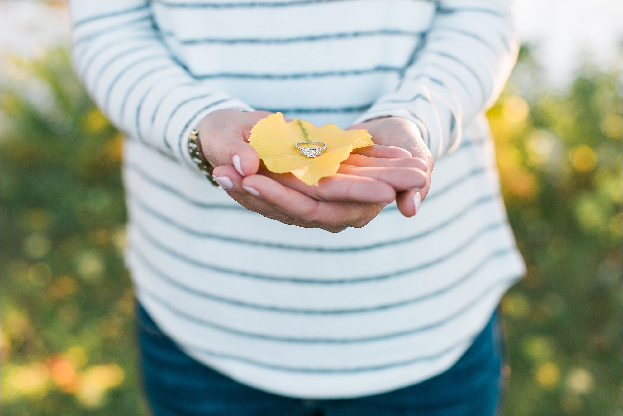 Engagement ring on fall leaf at Minneapolis Fall engagement session at Boom Island Park in Minneapolis photographed by Mallory Kiesow