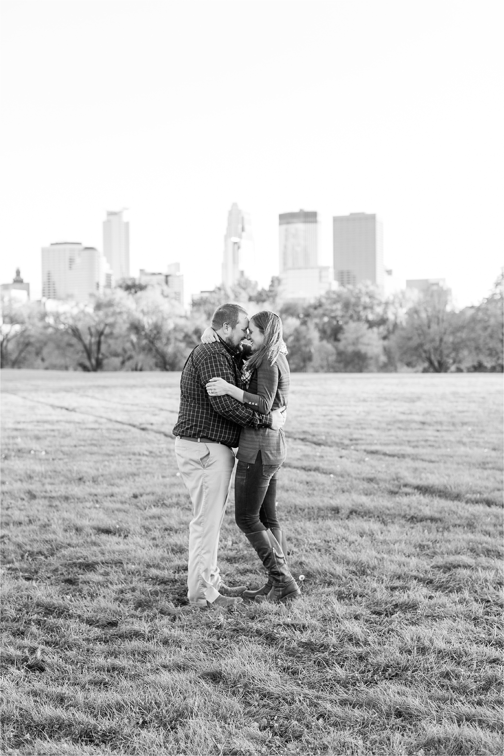 Engaged couple black and white photograph in front of Minneapolis skyline view at Minneapolis Fall engagement session at Boom Island Park in Minneapolis photographed by Mallory Kiesow