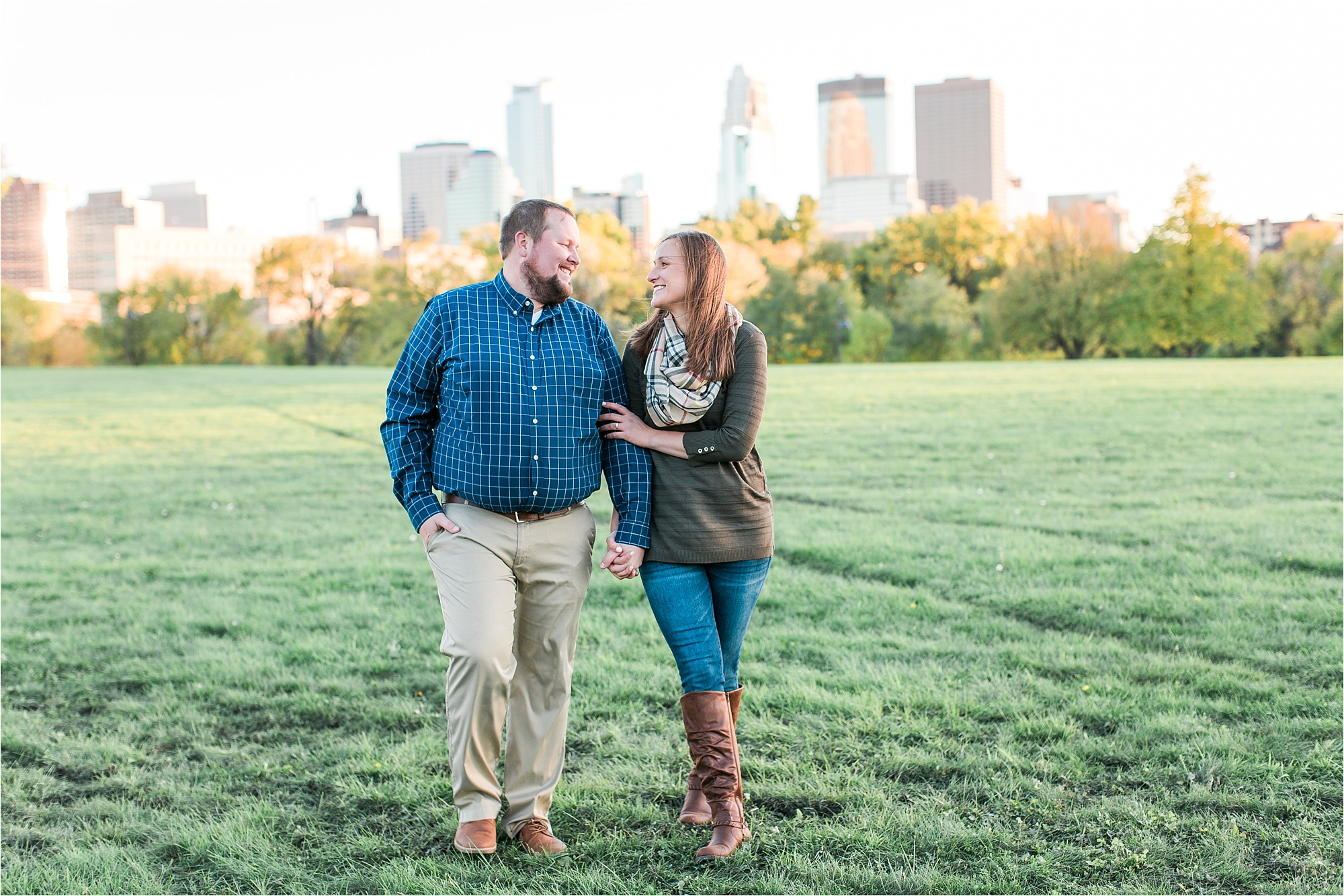 Engaged couple walking with Minneapolis city skyline in the background at Boom Island Park in Minneapolis Mallory Kiesow Photography