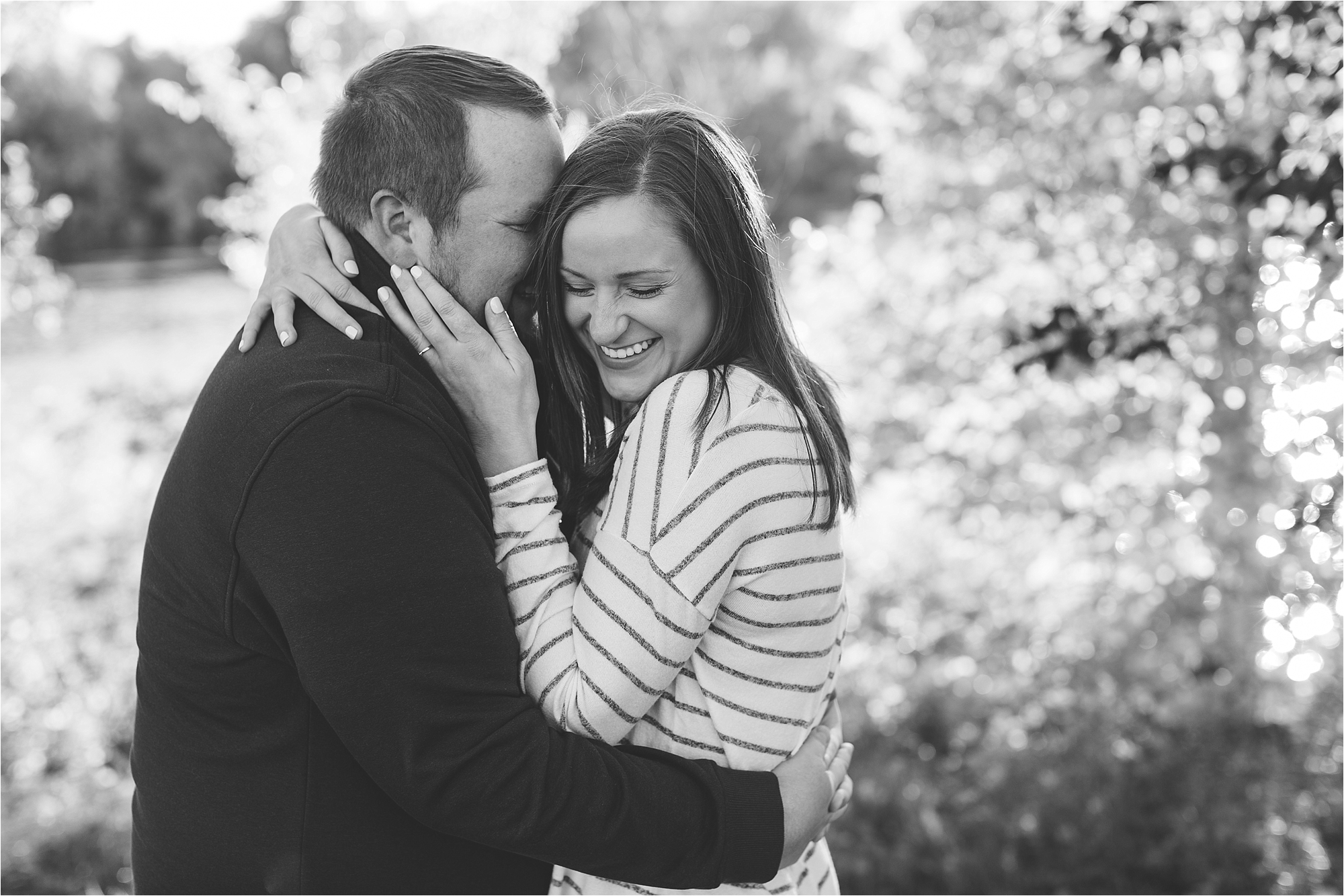 Black and white image of engaged couple embracing in Minneapolis fall engagement session at Boom Island Park in Minneapolis