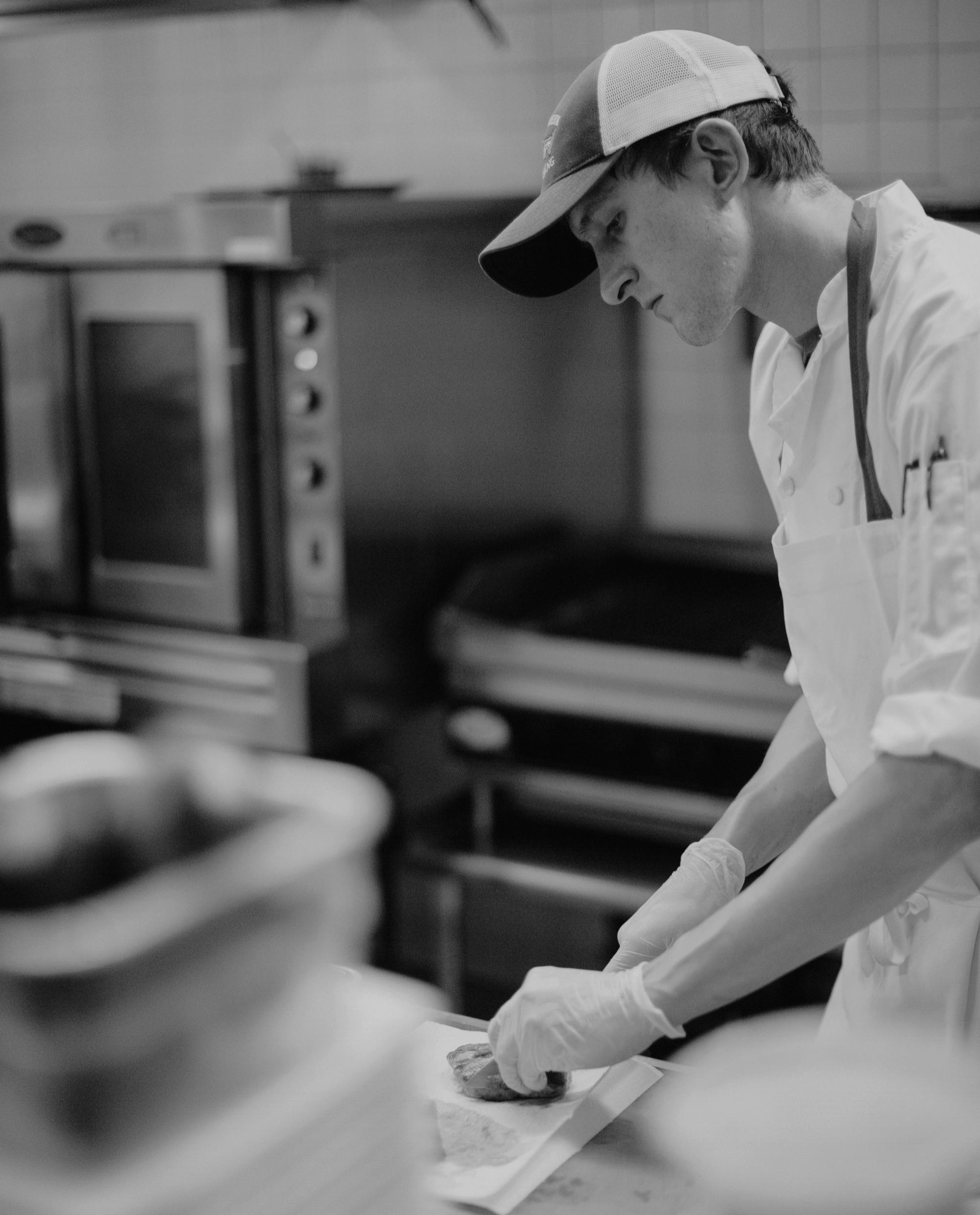 """Nick Boucher - Kitchen Manager & Sous ChefNick Boucher is a local gentleman with a long working history at the Joshua Wilton House. Beginning in 2012 as a dishwasher, Nick saw it as a """"foot in the door"""" for the culinary field. Steadily, Nick has trained with fantastic chefs and found his own voice & style in the kitchen. From intimate gatherings, to large weddings, Nick has maintained a steady hand and a good laugh through it all. In the Fall of 2018, Nick was promoted to Kitchen Manager, and works alongside our Executive Chef to train staff, create fantastic dishes, and experiment with new techniques and products. With a passion for not only food, but the Wilton House itself, Nick has been an encouraging force as we continue to adapt and push ourselves further. We're happy he has continued his growth with us."""