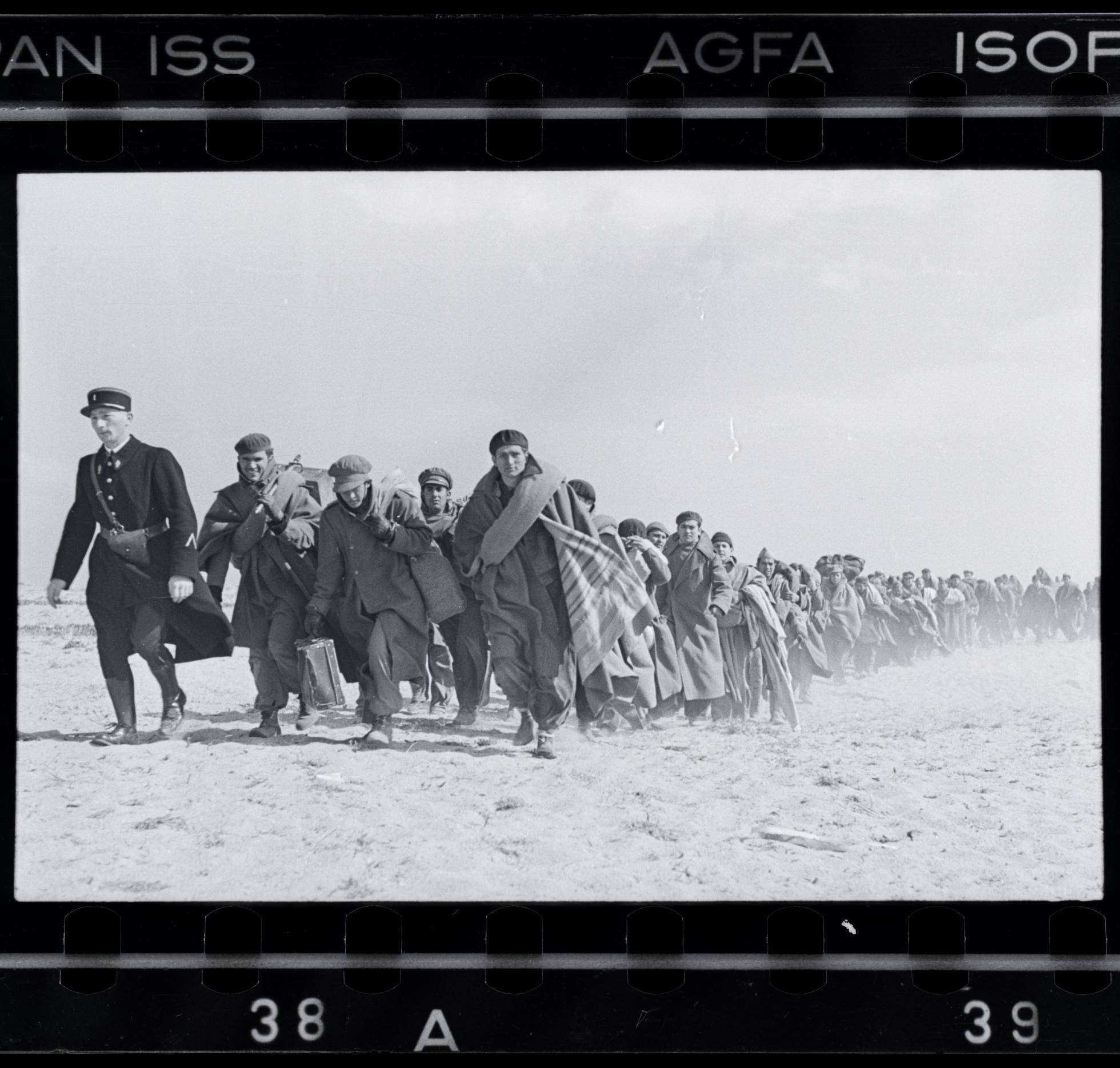 Robert Capa,  Refugees walking on the beach, in the French internment camp for Republican exiles, Le Barcarès, France, March 1939 .  Image credit: International Center for Photography / Magnum, via  Wikimedia Commons .