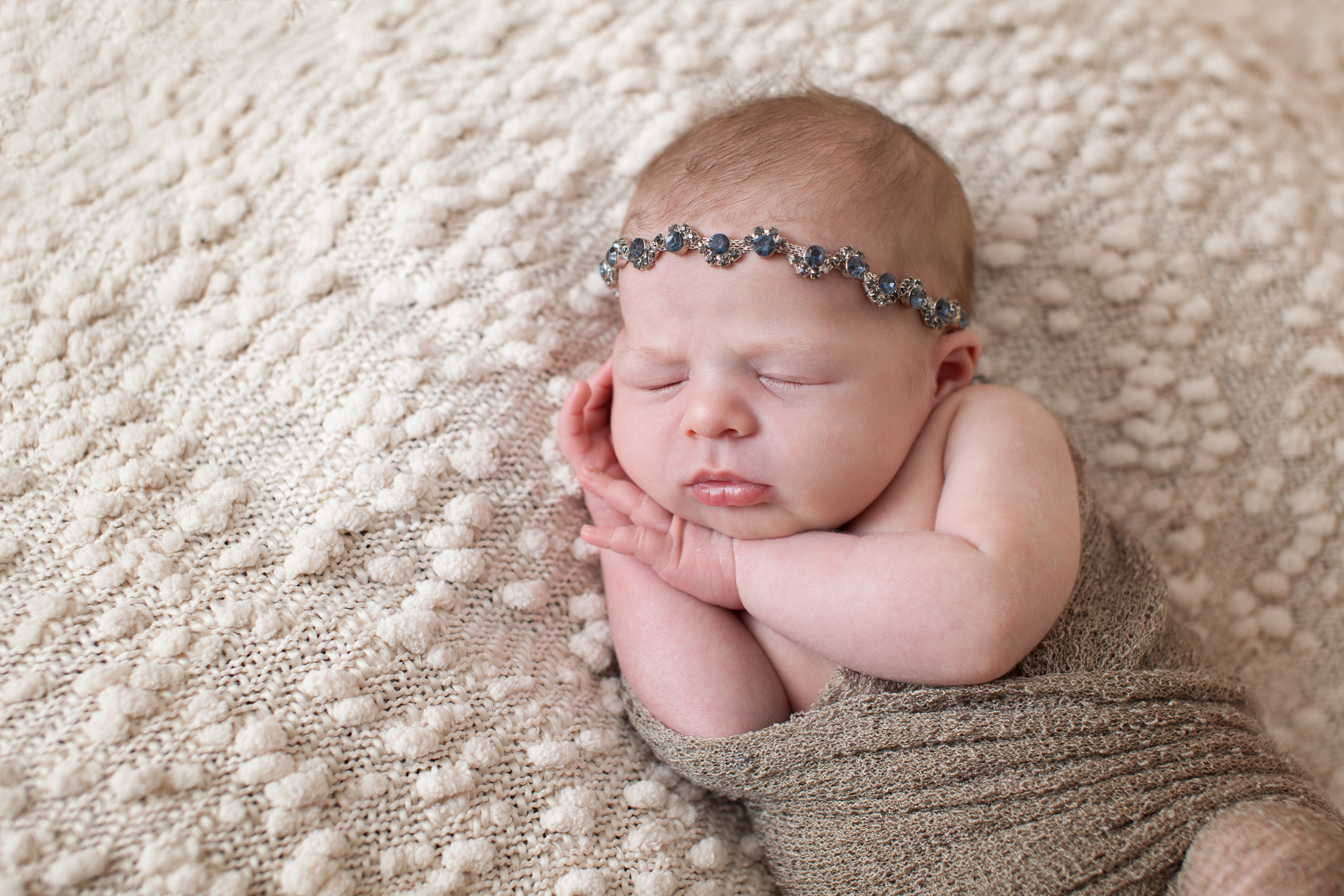 Columbus, Ohio photographer, Professional Portrait Studio, newborn photography. Infant in wrap with jewel tieback.