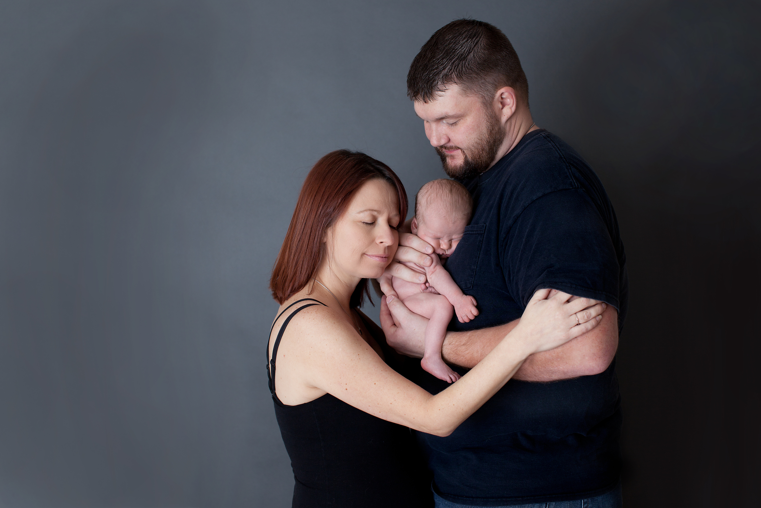 Columbus Ohio professional portrait photographer. Newborn baby photography. Mother and Father with infant son at Studio.