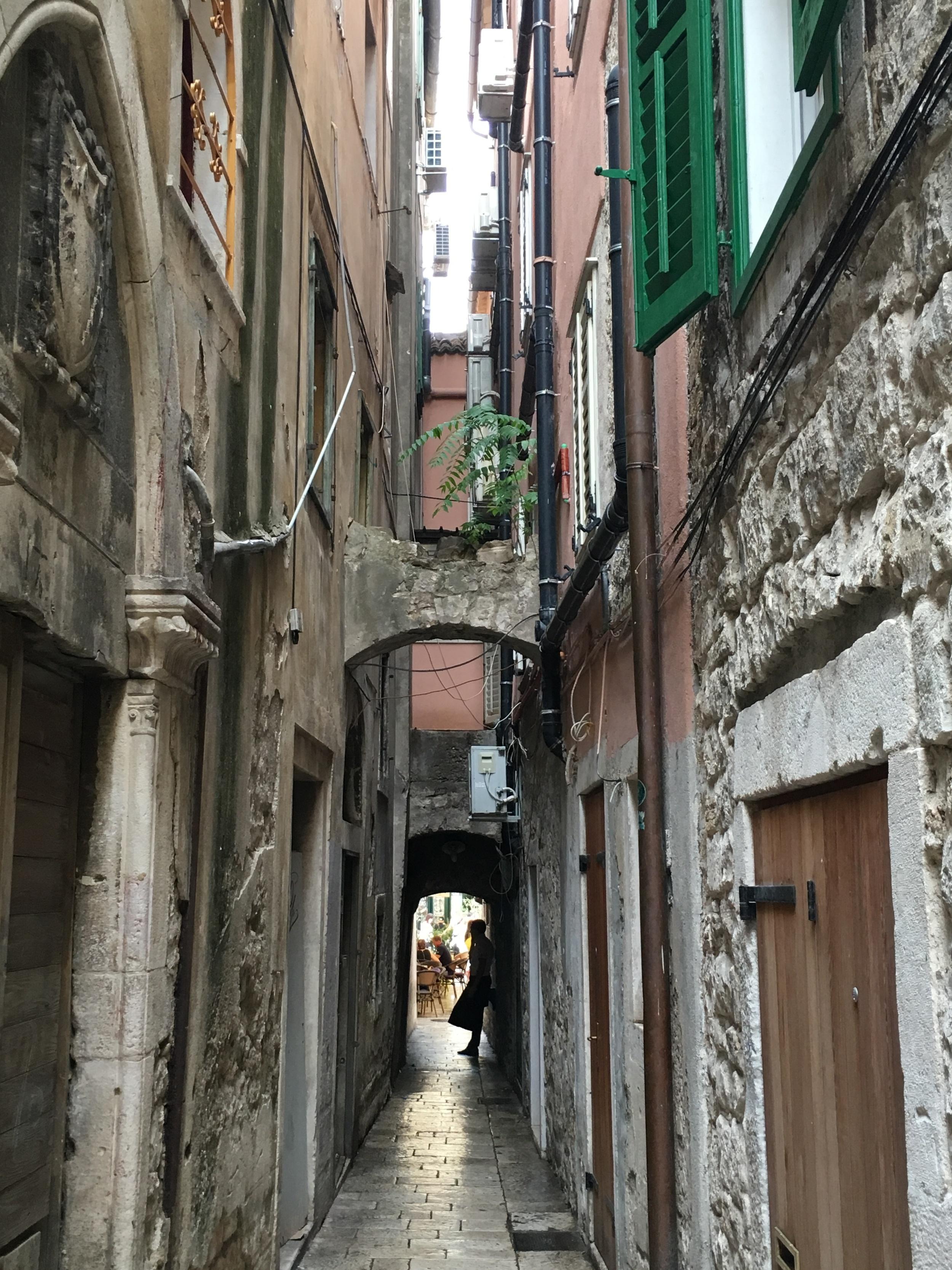 Another narrow street. Waiter taking a break from busy restaurant duties.