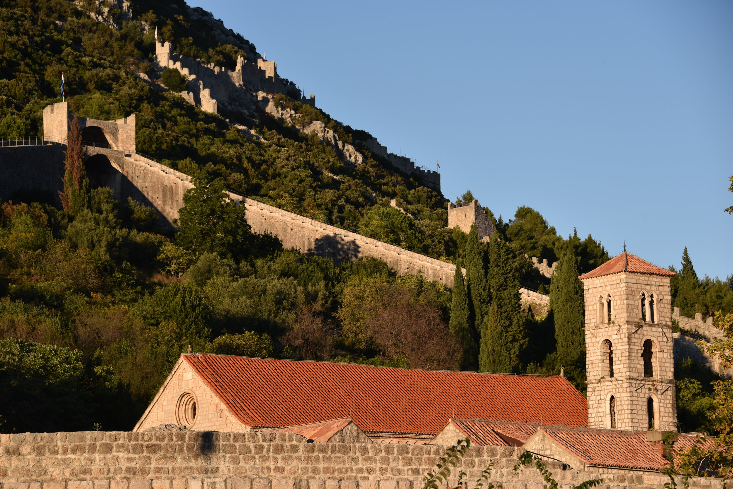 Walls of Ston at sunset, as viewed from outside the walls below.