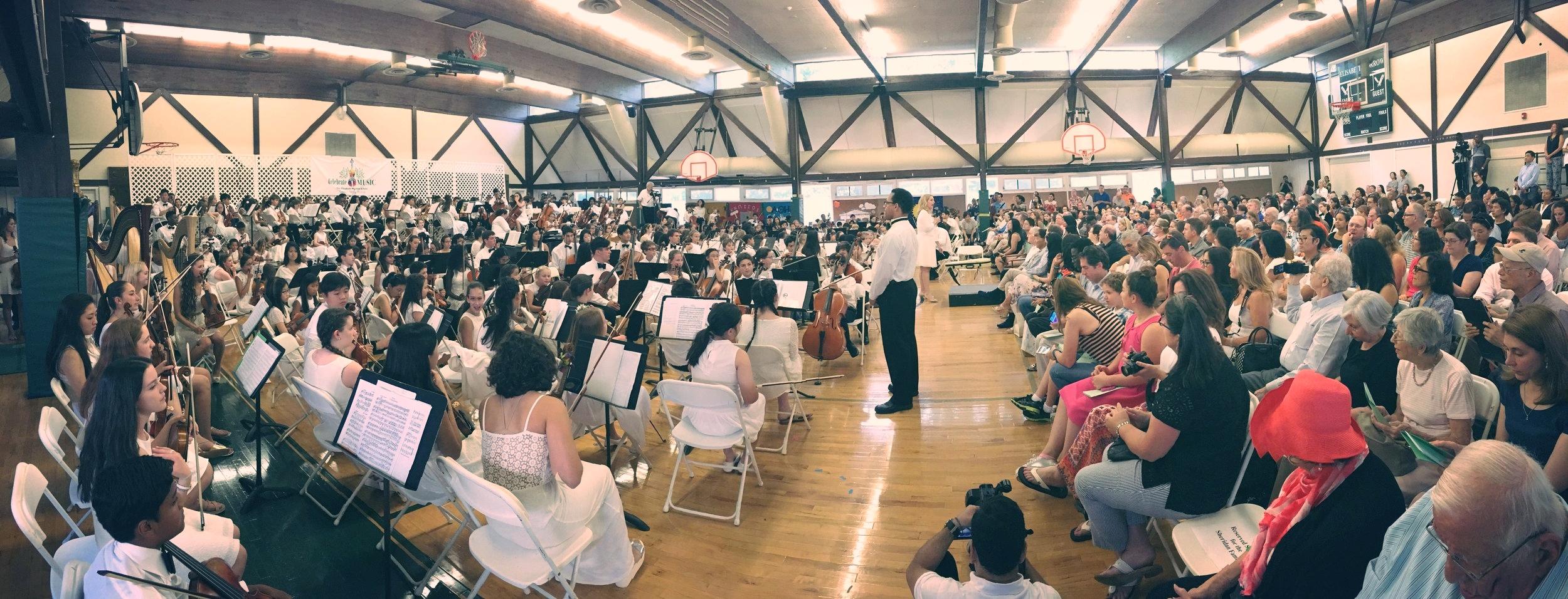最終日のコンサートの様子。左は生徒達のオーケストラ。右側にその演奏を見に来た家族達。