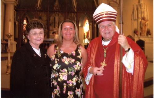 El Obispo Bradley con un adulto recién confirmada (centro) y su madrina
