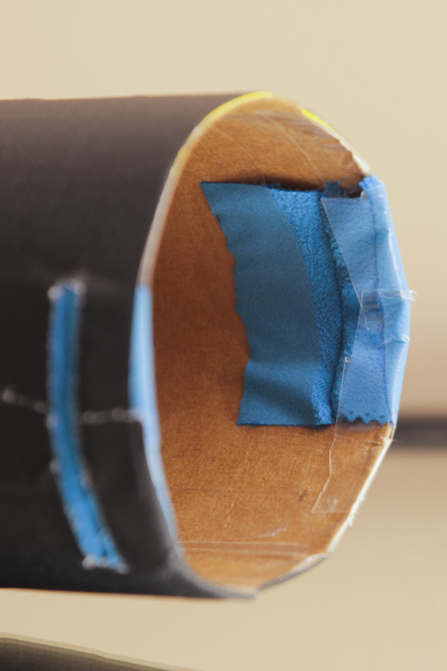 I made two narrow slits on opposite ends of the tube for the film to slide through.  To make sure the film didn't get all scratched up on the way through, I cut up a microfiber cloth to line each slit with.
