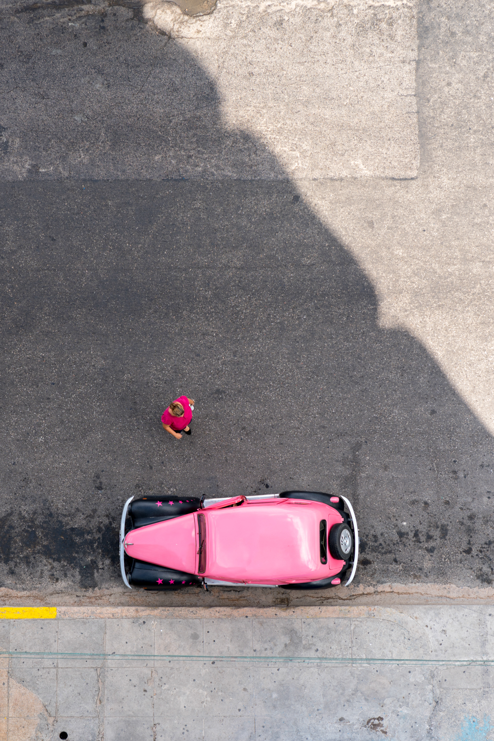 Looking straight down from our balcony, I caught this woman walking to her pink car.  Sony A7RII, Zeiss Batis 85mm f/1.8 (iso50, f/4, 1/200s)