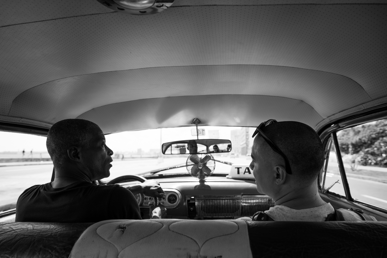 We caught a taxi to Habana Vieja. This is Efrain chatting with the driver.  Sony A7RII, Zeiss Batis 18mm f/2.8 (iso100, f/4, 1/400s)