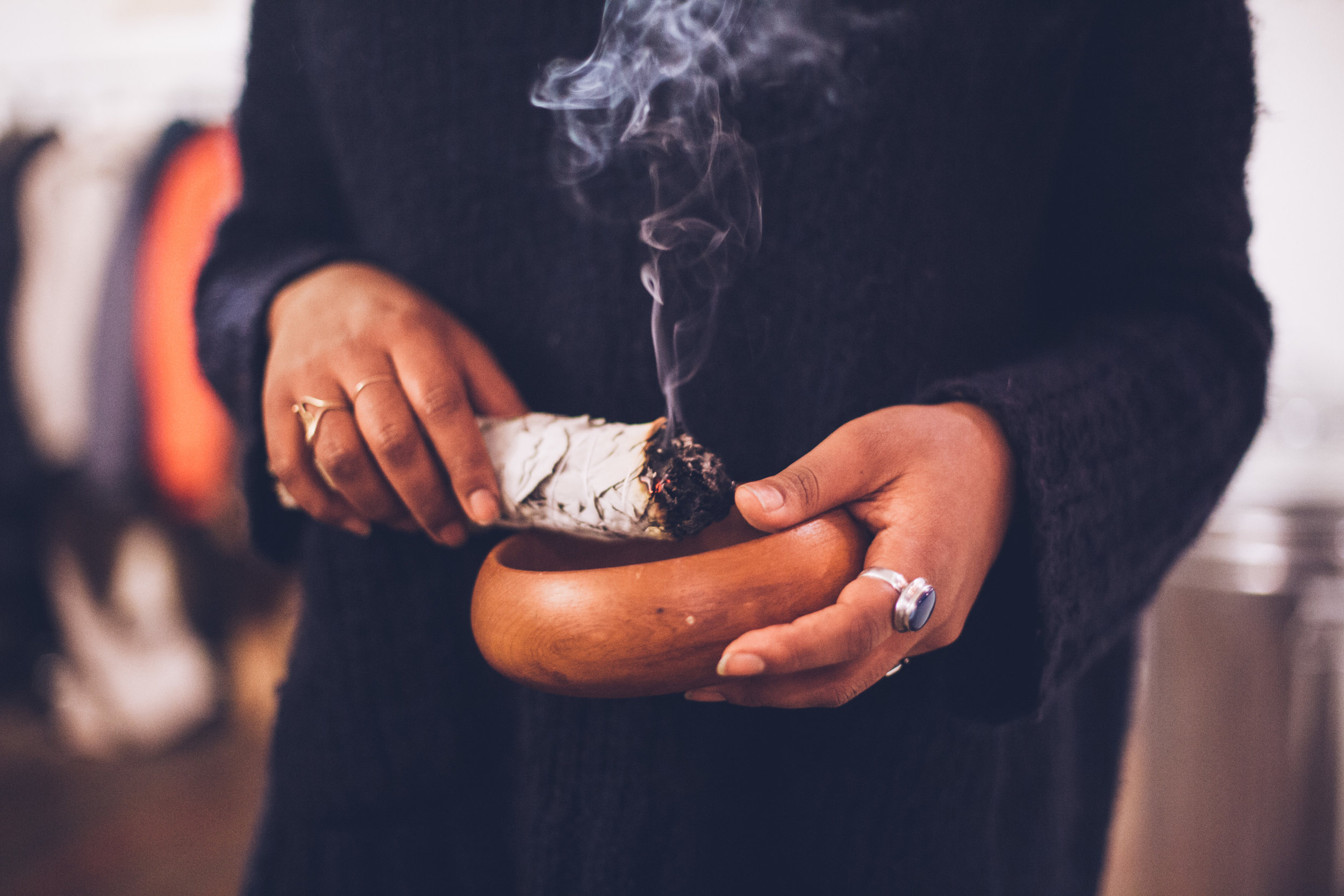 [Photograph of a woman holding a burning stick of sage and a wooden bowl in her hands.]