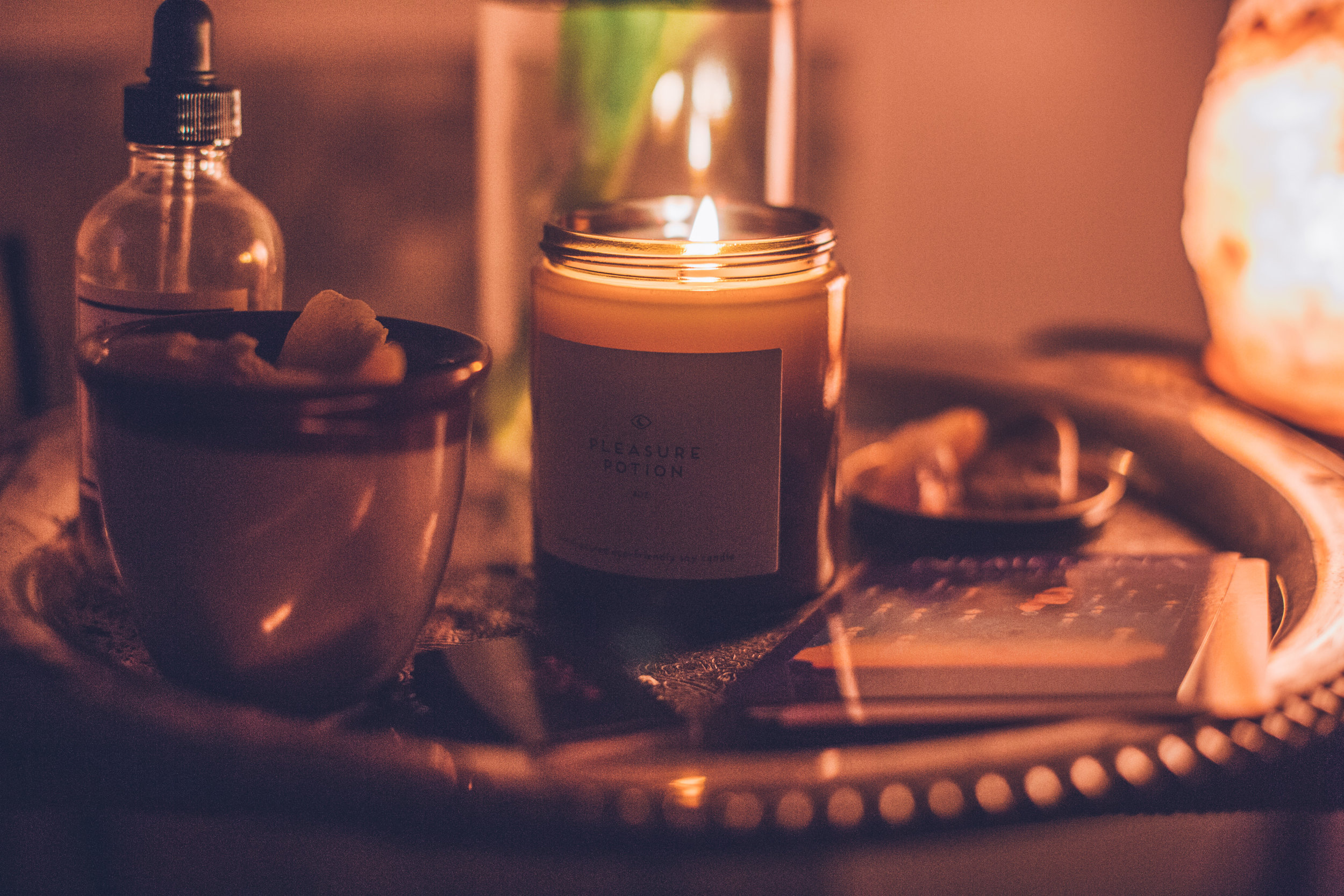 [Photograph of a lit candle surrounded by cards, a bottle of oil and a Himalayan salt lamp]