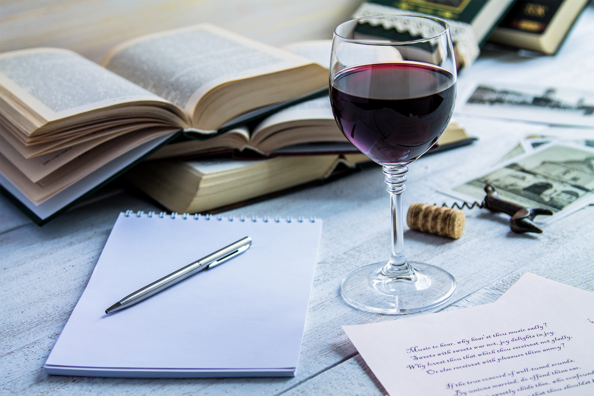 Glass of red wine and a book on a white wooden background-1.jpg