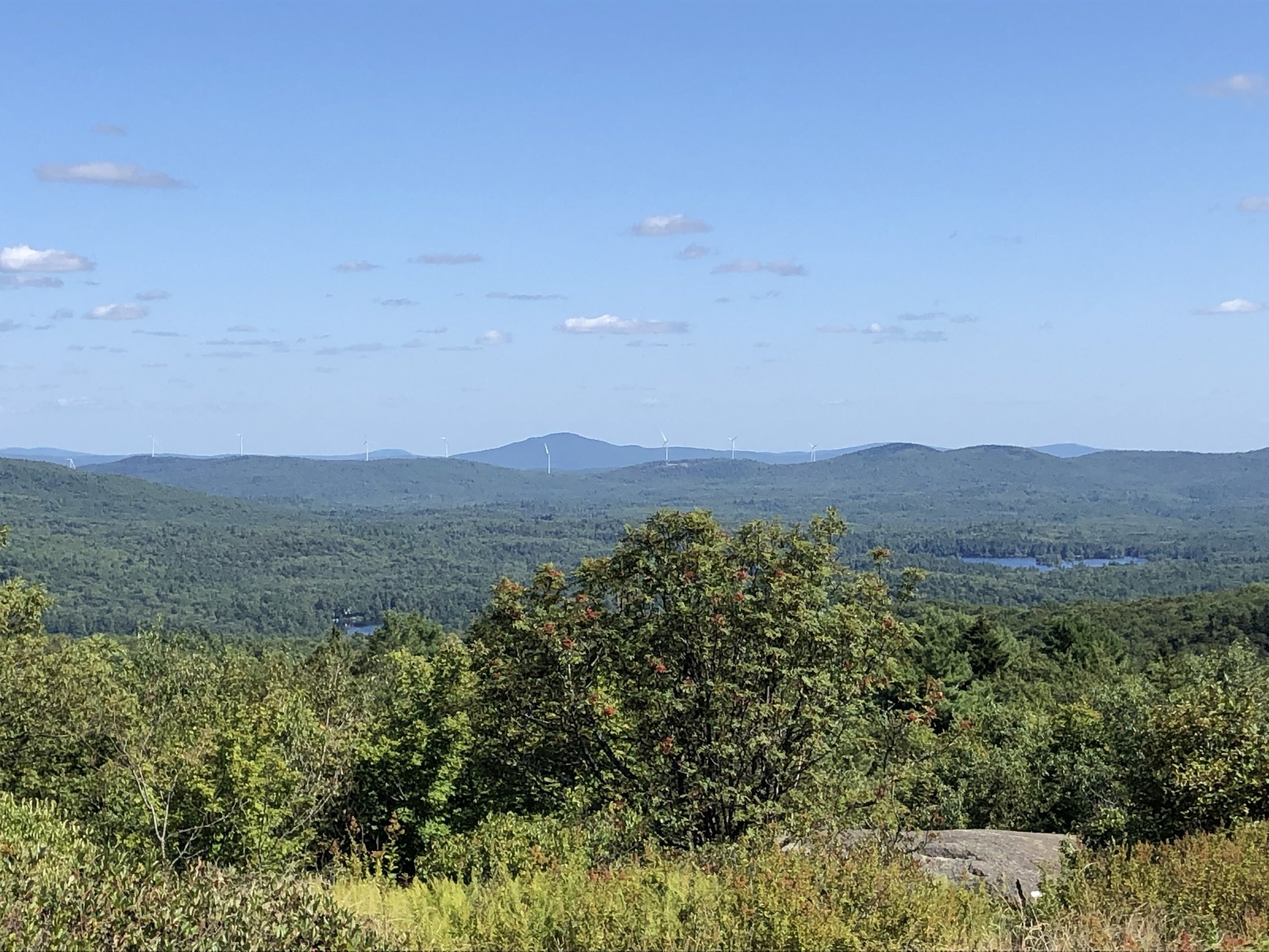 The view from Pitcher Mountain in Stoddard.  Island Pond is on the right.  The line of new windmills in Antrim is along the ridge in the distance.