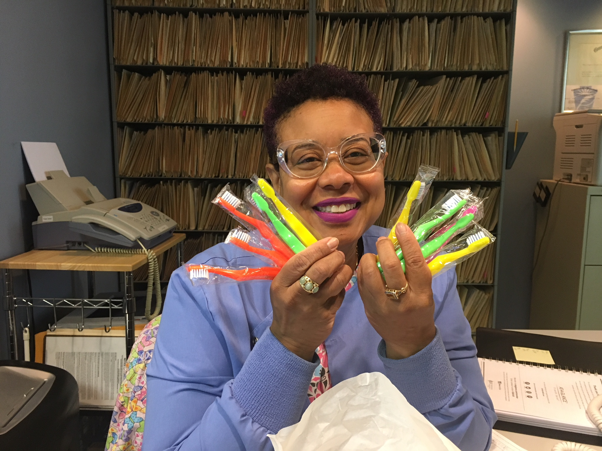 Thanks to ALL donors who helped us fill the bags without draining our budget! Dana of Dr. Philip Springer's office holds kids toothbrushes for our bags.