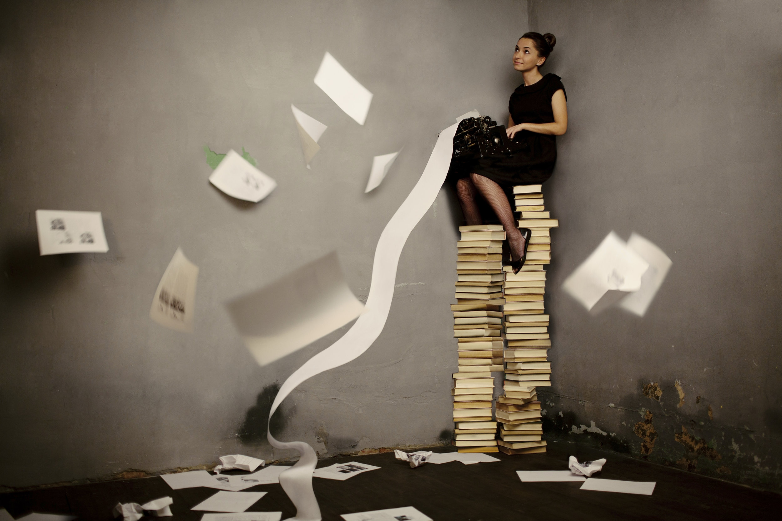 woman on a pile of books, overwhelmed by information, typing manically