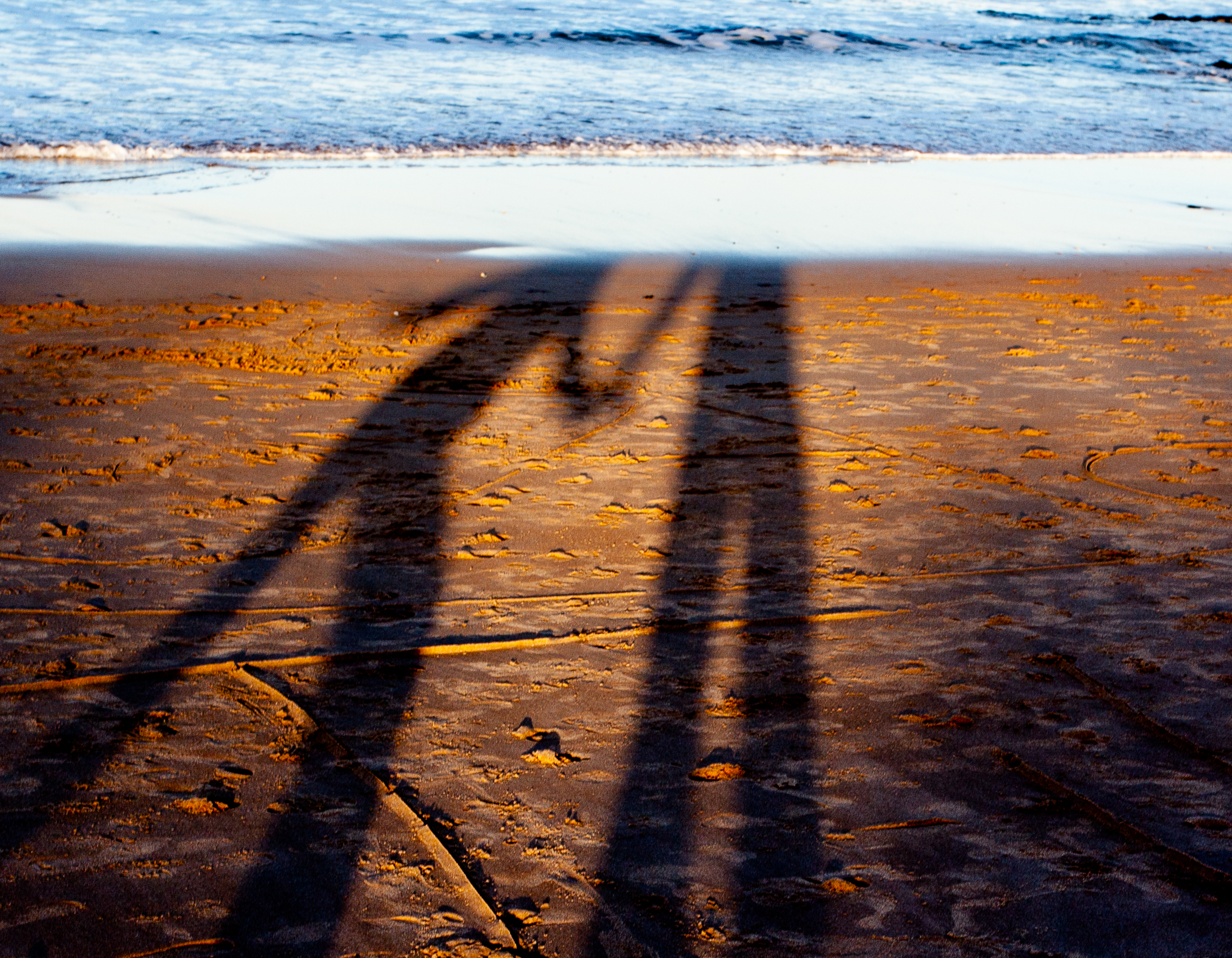 the shadow of me holding hands with Clare on the beach