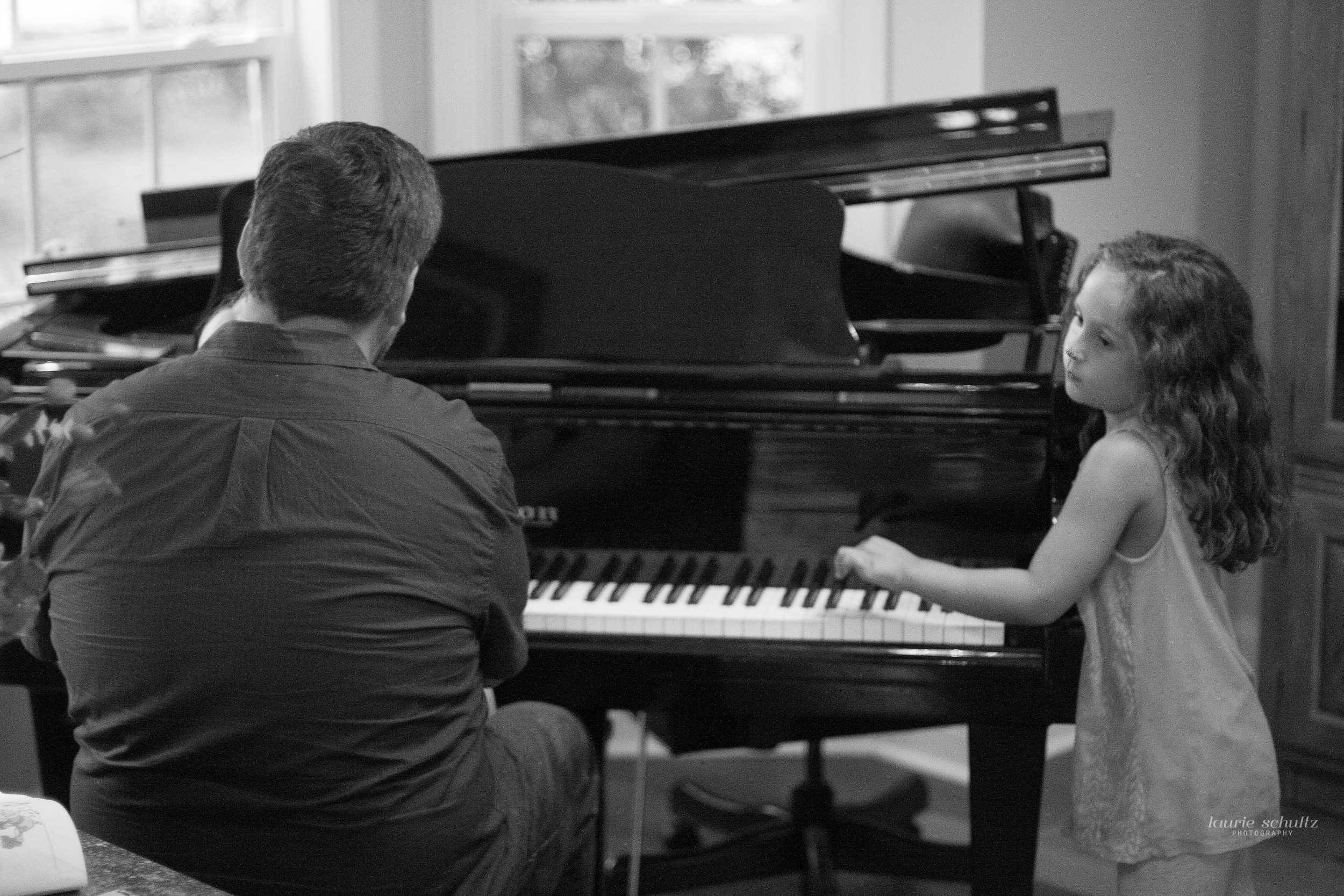A dad and his little girl playing piano