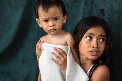 Nila, one of the children who is growing up at the Bantar Gebang landfill, bathes her little brother in their family's shelter.