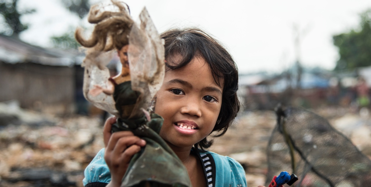 Sita, one of the young children whose families call the landfill their home, searches for toys amongst the rubbish.