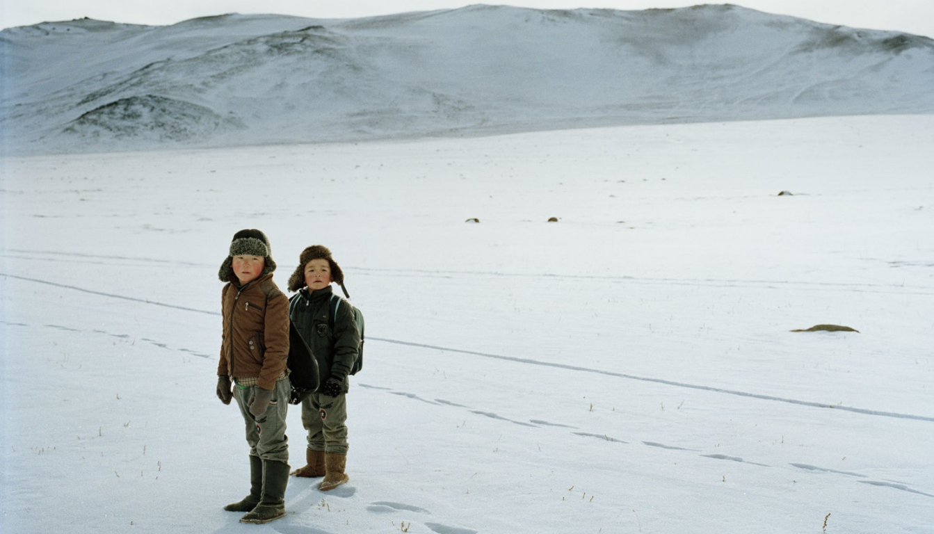 Two schoolboys, wearing fur-lined boots, walk home through the snow near the village of Altai (Алтай) in the far west of Mongolia.