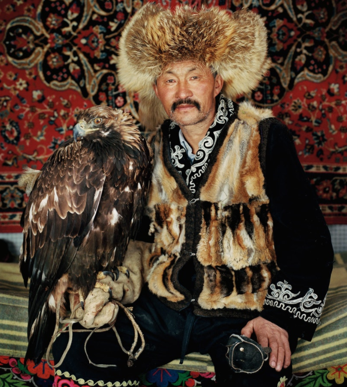 Dalaikhan, a champion hunter, with his 2-year-old eagle. He is wearing fox-skin clothes from previous successful hunts.