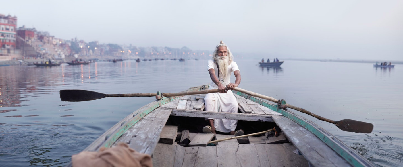 Above: Ascetic priest Baba Vijay Nund rows a boat along the Ganges River.