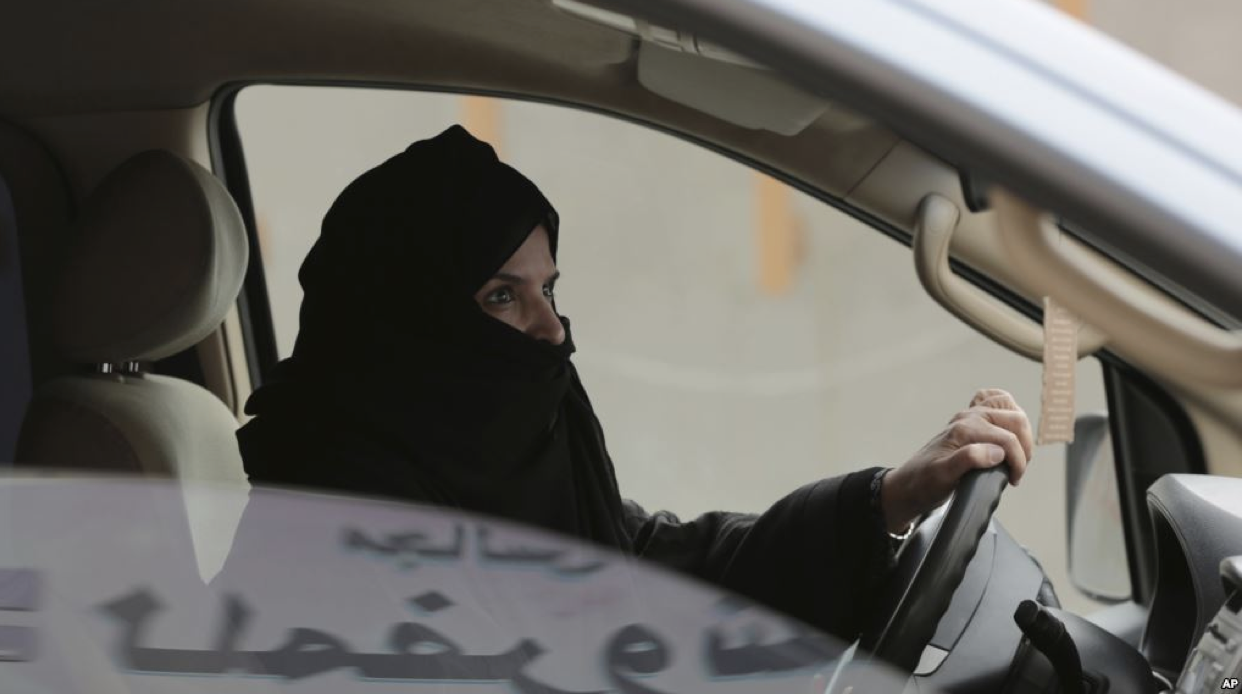 """Aziza Yousef drives a car on a highway in Riyadh, Saudi Arabia, as part of a campaign to defy Saudi Arabia's ban on women driving, March 29, 2014. (AP Photo/Hasan Jamali, File)"""