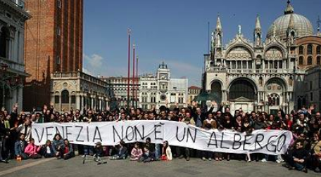 Residents pose with sign reading: Venice is not a hotel. Image Credit: The Telegraph