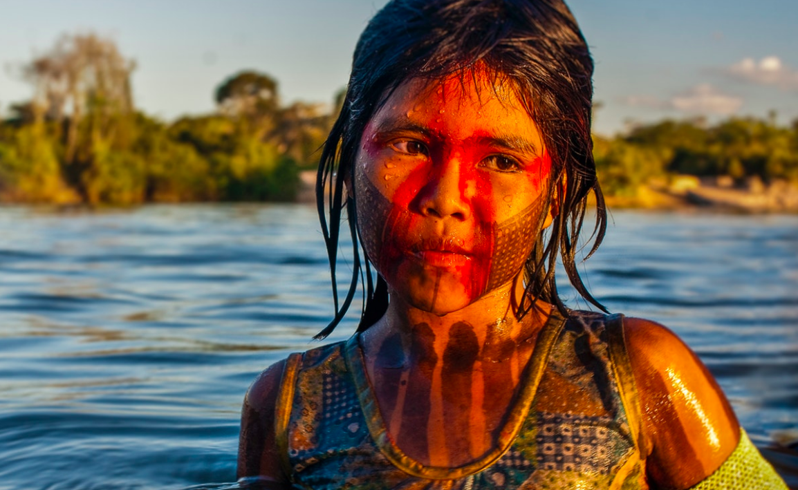 The Xingú river is intimately woven into the fabric of Kayapó life. This young girl's eyes speak of a beloved waterway about to be dammed forever, of pride in her people's traditions, of fear for a future unknown, and of the innocence that every child deserves to live with.    Brazil