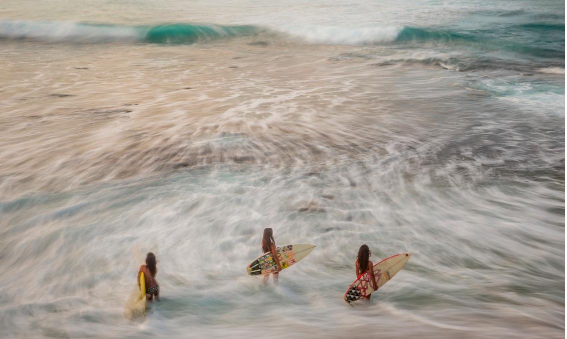 Three Hawaiian sisters wait for the waves in Makaha Beach, Oahu.    Hawaii, United States of America