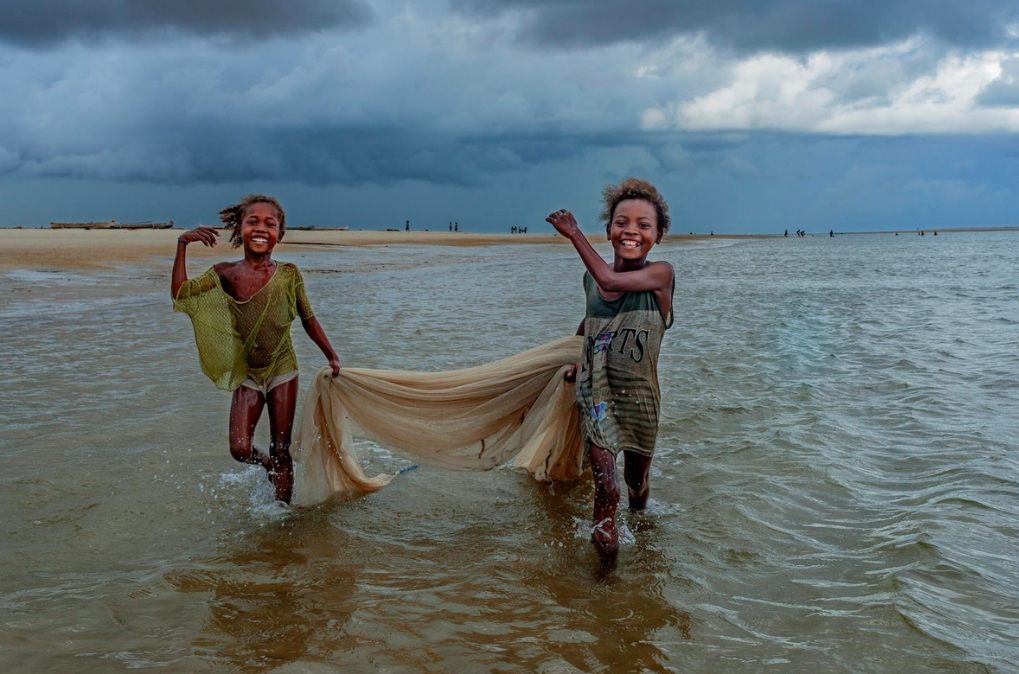 Two young Vezo girls, like water nymphs more at home in the ocean than on land, gather fish for their family's dinner.    Madagascar