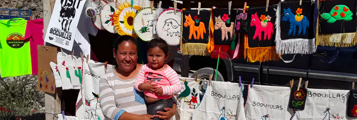 Lucia Orosco holding her daughter, Arely, in Boquillas. Much of the embroidery created here reads 'no el muro' (no wall). Matthew Moran,  CC BY-ND