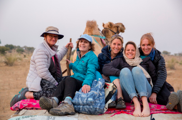 Purposeful Nomad Founder, Caitlin Murray, (second from right) and women's sustainable travel group gather after a village homestay and camel trek in the Thar desert, India. Jessica Scranton. Purposeful Nomad.
