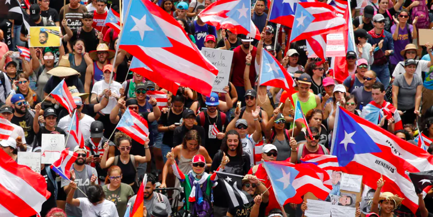 People wave Puerto Rican flags as they attend a rally to celebrate the resignation of Puerto Rican Governor Ricardo Rosselló in San Juan, Puerto Rico on July 25.  REUTERS/Marco Bello