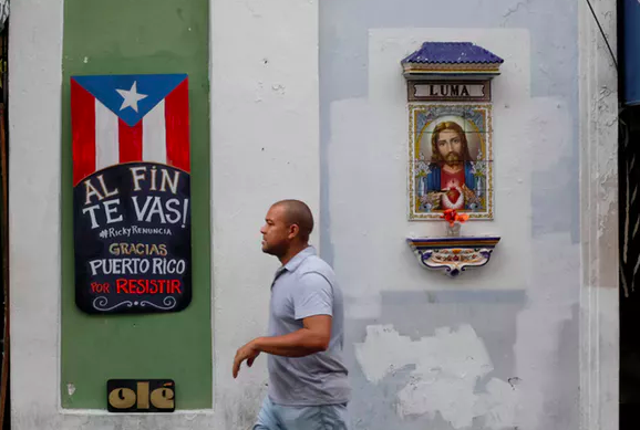 A man walks past a sign that reads 'You are finally leaving. Ricky resign. Thanks Puerto Rico for resisting' on the street that leads to La Fortaleza, the official residence of the governor of Puerto Rico. REUTERS/Marco Bello