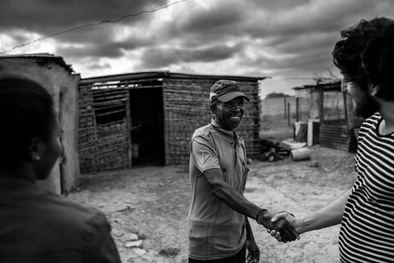 Meeting with Sam, a Langbos community leader we've worked with since 2015. In 2018, we sponsored Sam's daughter Lindelwa to study at the South Africa College for Tourism. Langbos, 2018. Photo by  Kavish Rajpaul.