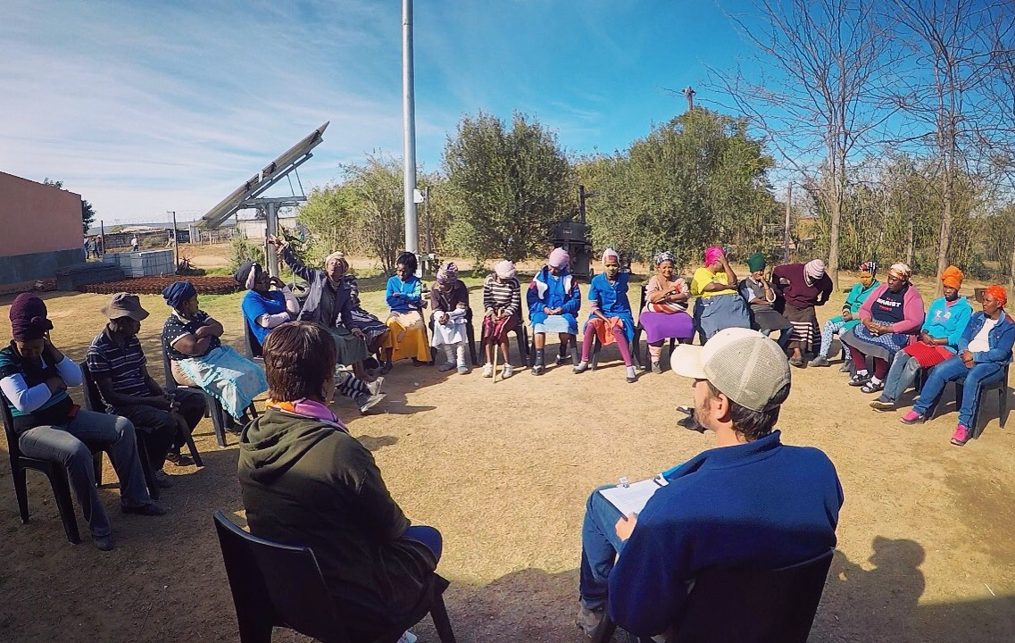 Ryan Thompson, a student from New York University School of Medicine, conducting a community meeting as part of his health needs assessment in Langbos, July 2017.