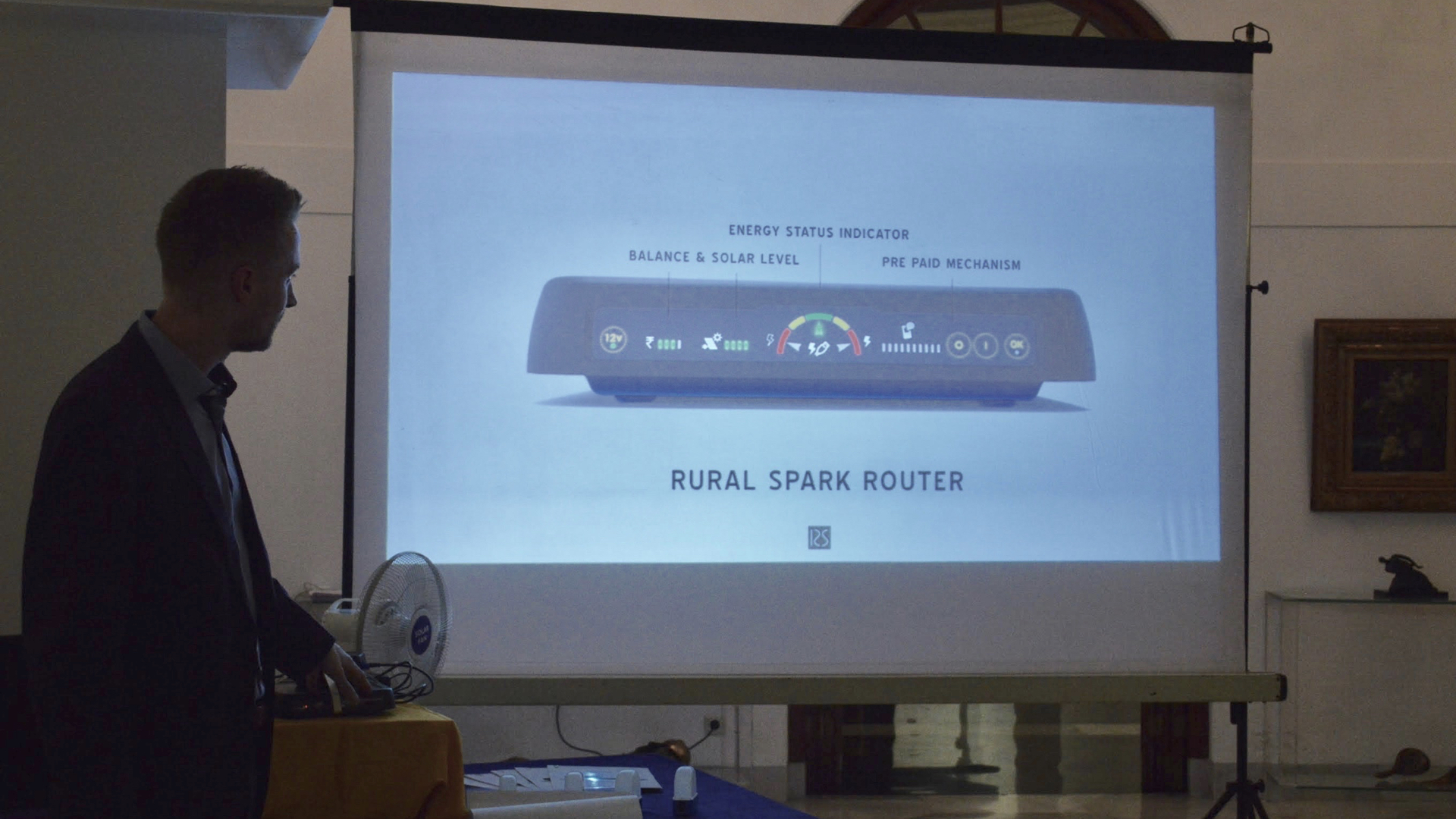 Evan showcasing the new Rural Spark Router with prepaid module, displaying solar and credit balance and allowing for all 5V and 12V applications to be charged.