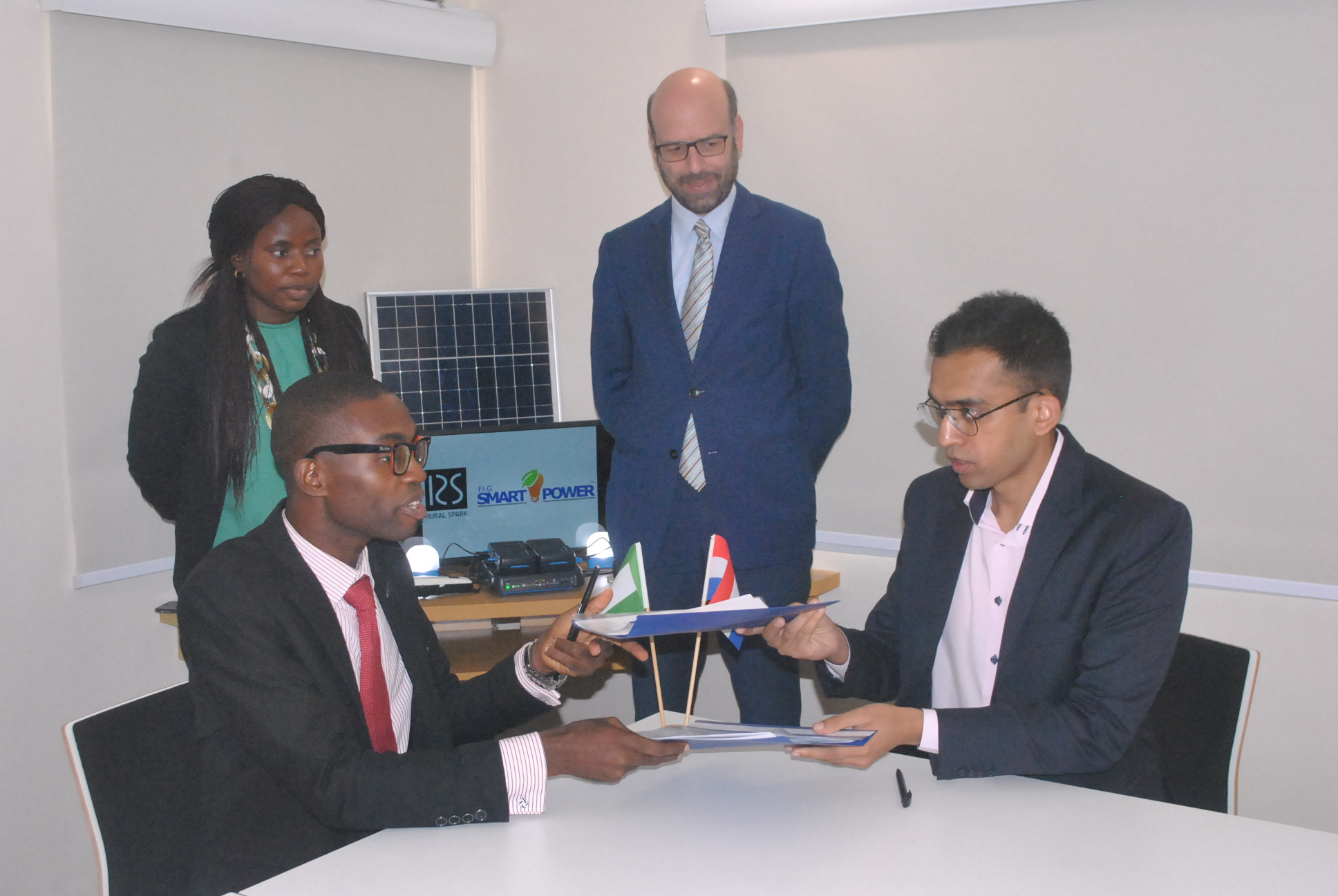 Tolu-tope Dade (CEO Smartpower) and Shagun Jain (Rural Spark) signing a partnership for electrification of rural Nigeria, overlooked by Michel Deelen (Deputy Ambassador of the Kingdom of the Netherlands to Nigeria) and Sonia Fujusigbe (Economic Trade and Investment Affairs, Embassy of the Kingdom of the Netherlands).