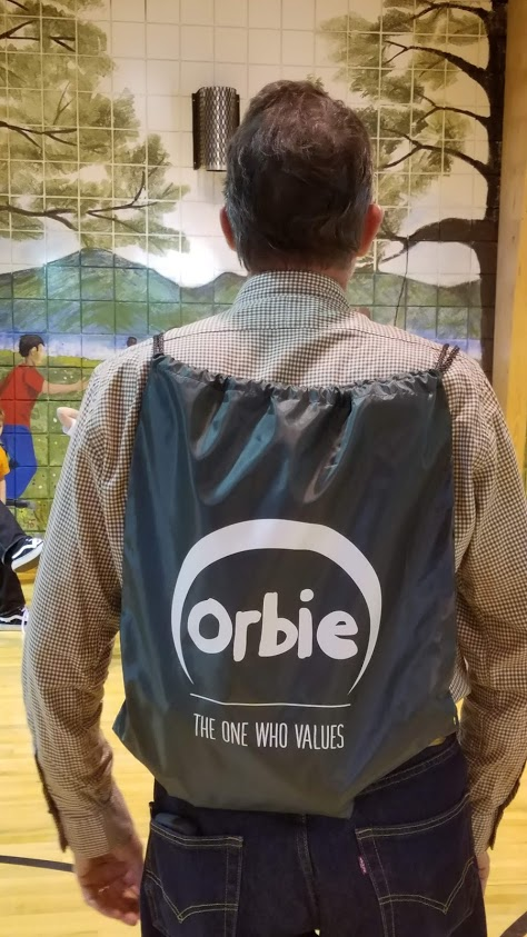 Board member, Brian, models the Orbie backpacks for the kids.